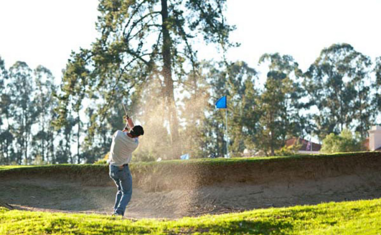 A golfer escapes from a sand trap on the course at Blacklake Golf Resort